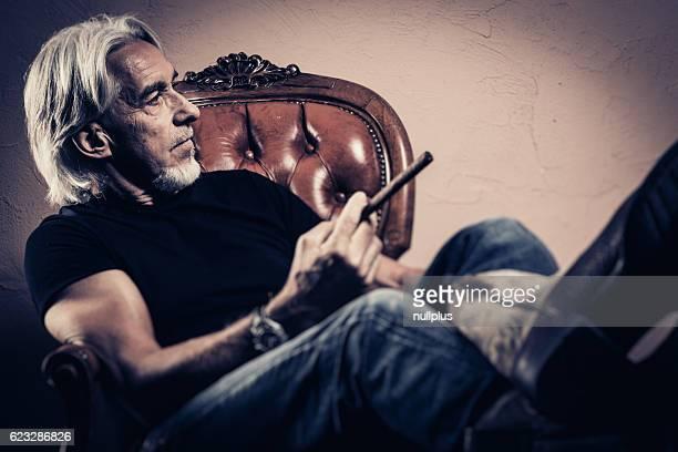 senior man sitting in armchair, studio portrait - contraste alto fotografías e imágenes de stock