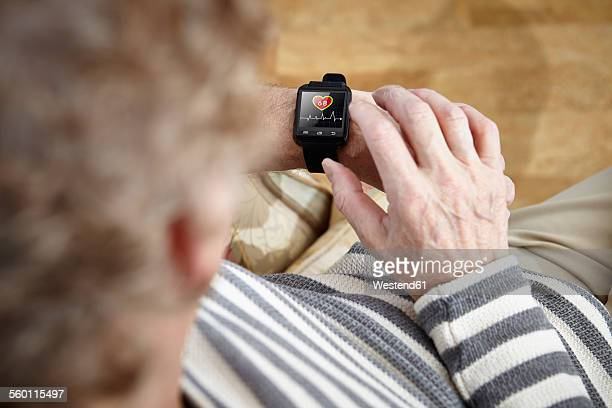 Senior man sitting in armchair using smartwatch