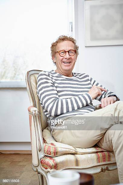 senior man sitting in armchair using smartwatch - thick rimmed spectacles stock photos and pictures