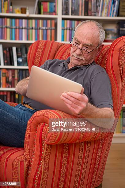 senior man sitting in armchair using tablet computer - einzelner senior stock-fotos und bilder