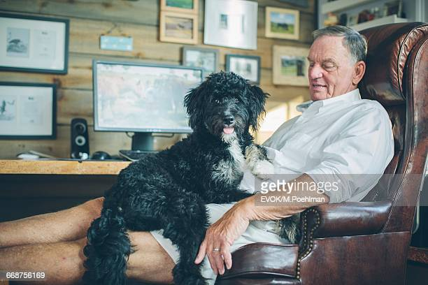 Senior man sitting in armchair with dog on his lap