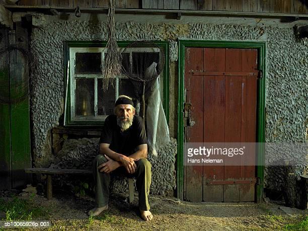 Senior man sitting in front of hut, portrait