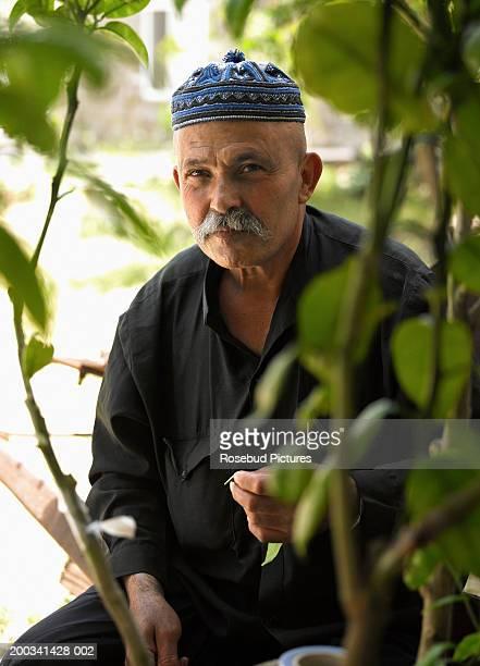 senior man sitting in garden, portrait - israeli men stock photos and pictures
