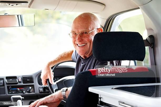 Senior man sitting in his campervan looking happy