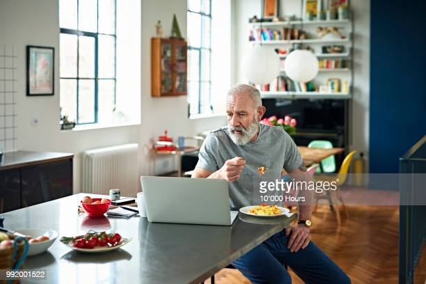 senior man sitting in kitchen eating breakfast and looking at laptop - article stock pictures, royalty-free photos & images