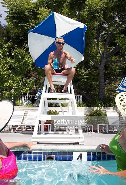 Senior man sitting in lifeguard tower.