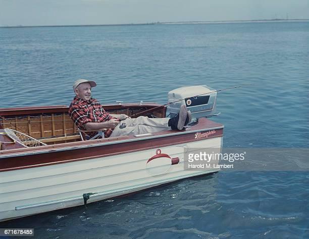 'Senior Man Sitting In Motor Boat, Fishing '