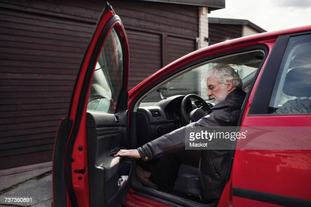 Senior man sitting in red car and closing door against garage