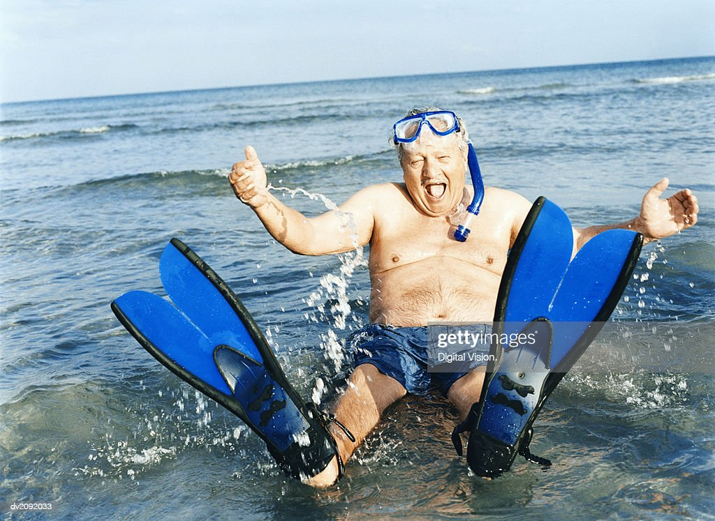 Senior Man Sitting in Shallow Sea Wearing Flippers, Scuba Mask and a Snorkel : Stock Photo