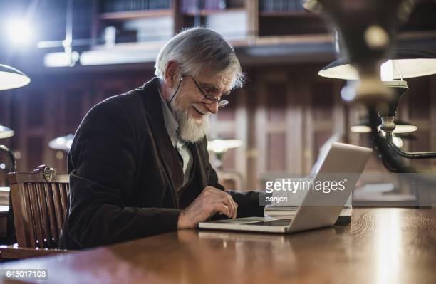 ältere mann sitzt in der bibliothek und mit laptop - college professor stock-fotos und bilder