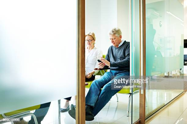 senior man sitting in waiting room using mobile phone - patient room stock photos and pictures