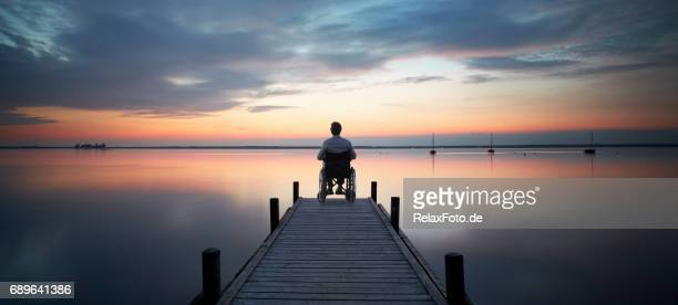 senior man sitting in wheelchair at the end of lakeside jetty watching majestic cloudscape at dusk - assistive technology stock photos and pictures