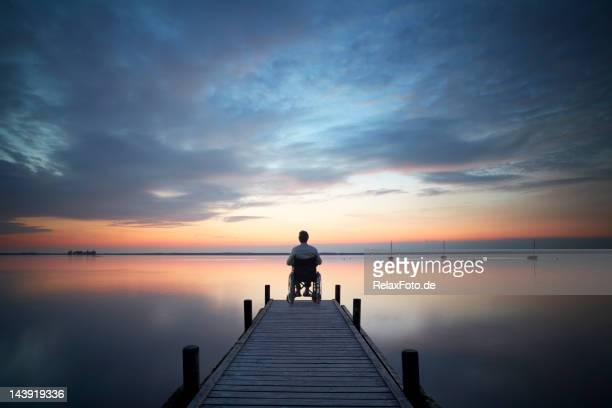 Senior man sitting in wheelchair on jetty at sunset