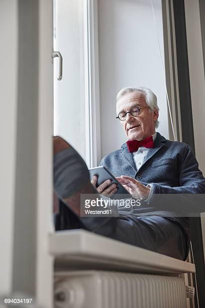 Senior man sitting in windowsill using tablet