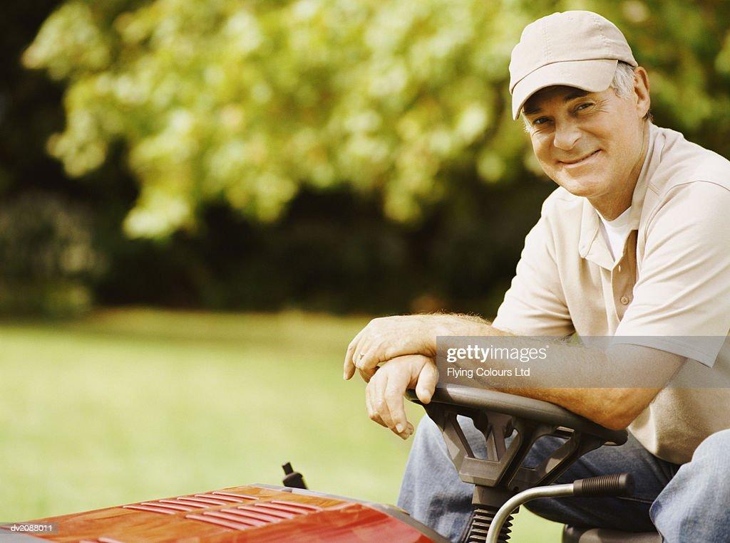 Senior Man Sitting on a Motorised Lawn Mower : Stock Photo