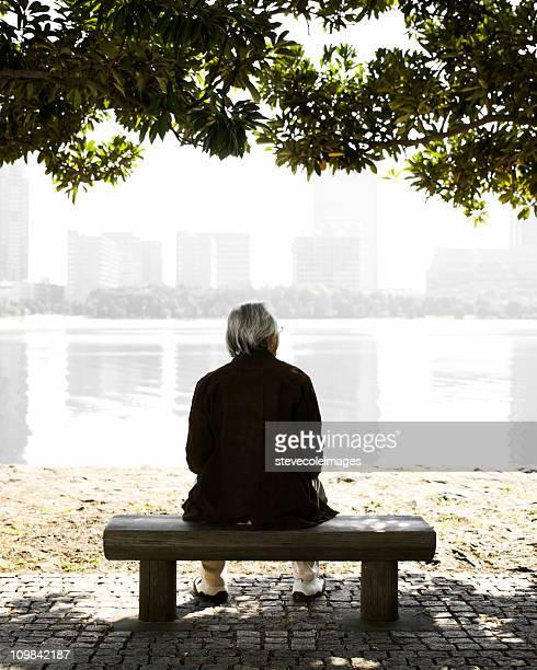 sênior homem sentado em um banco de parque - só um homem idoso - fotografias e filmes do acervo