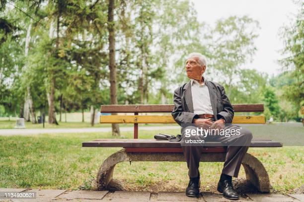 senioren-mann sitzt auf einer parkbank - sitzbank stock-fotos und bilder