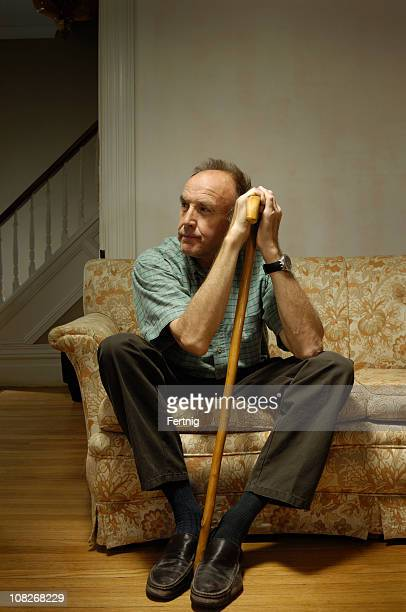 Senior man sitting on a sofa and leaning with cane