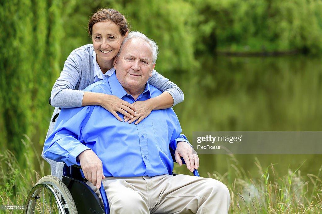Senior man sitting on a wheelchair with caregiver : Stock Photo
