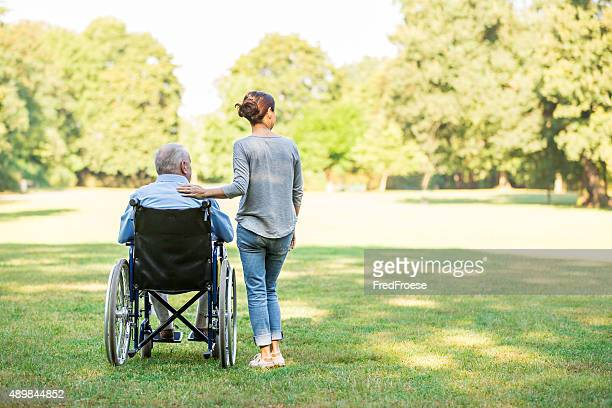 Senior man sitting on a wheelchair with caregiver