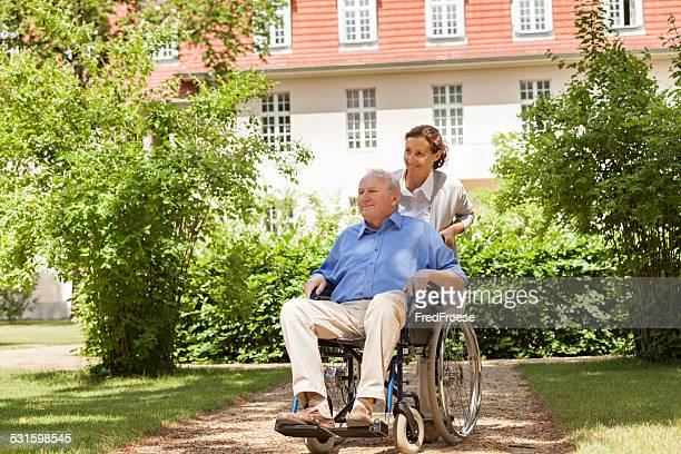 Senior man sitting on a wheelchair with home caregiver