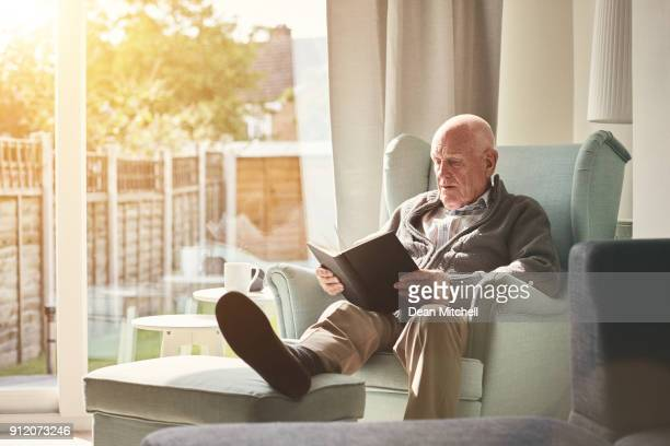 senior man sitting on arm chair and reading a book - cardigan sweater stock pictures, royalty-free photos & images