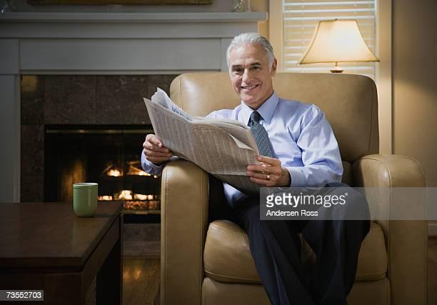 senior man sitting on arm chair, holding newspaper, smiling, portrait - einzelner senior stock-fotos und bilder
