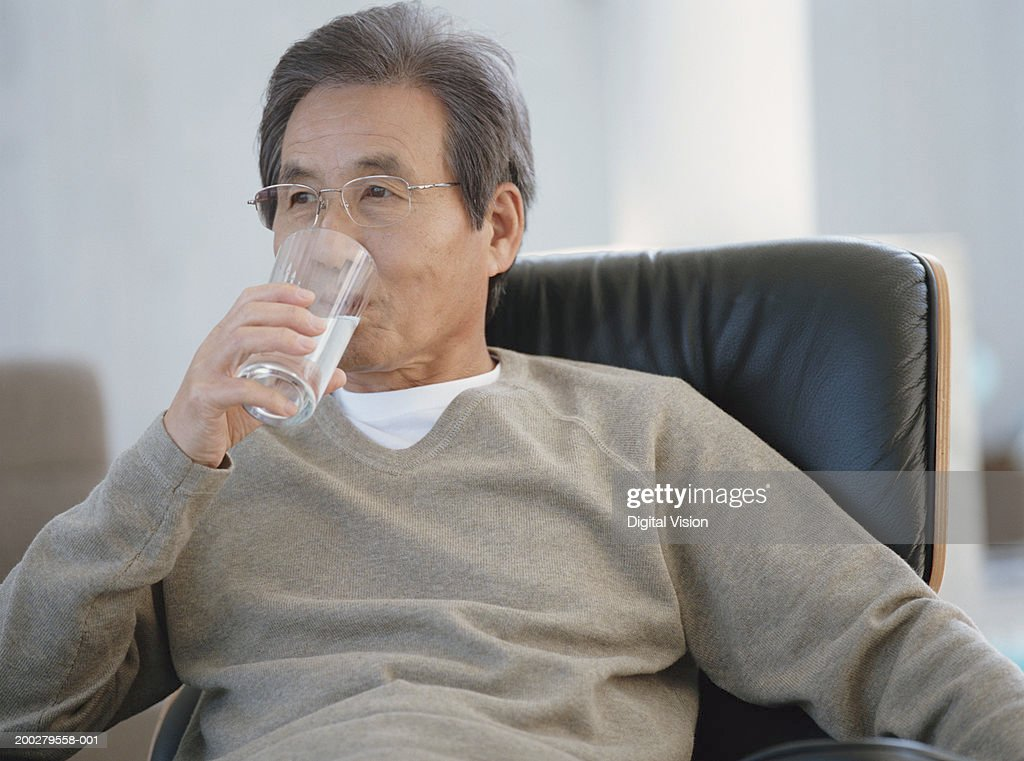Senior man sitting on armchair drinking glass of water : Stock Photo