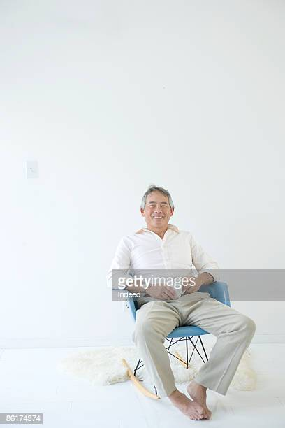 Senior man sitting on armchair, smiling, portrait
