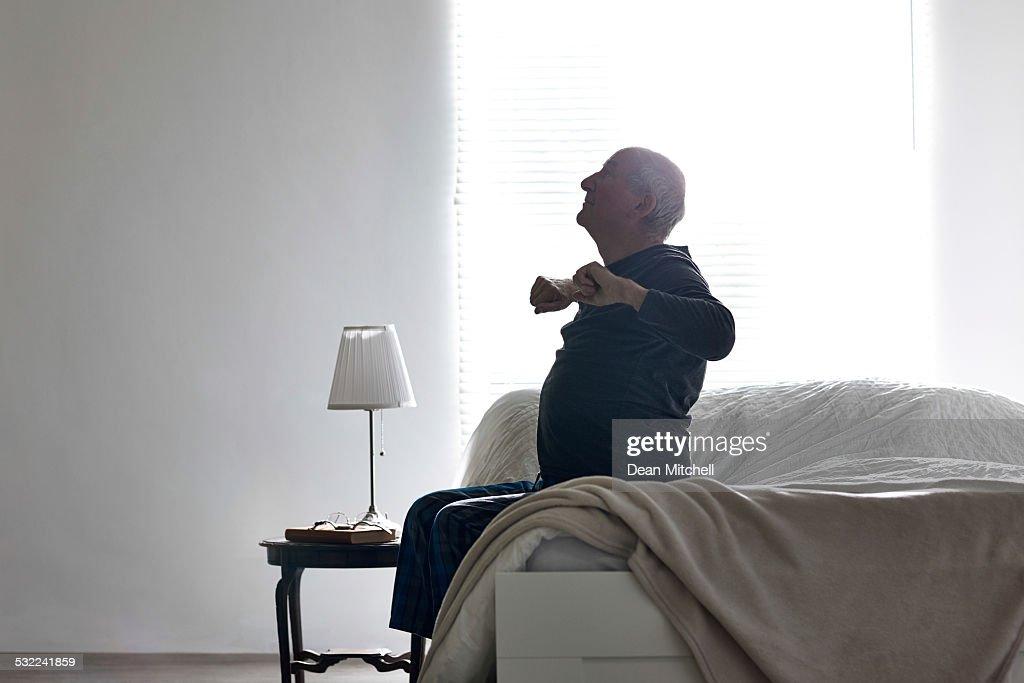 Senior Mann, sitzend auf dem Bett Dehnen der Arme : Stock-Foto