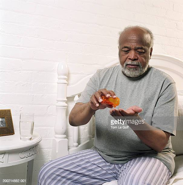 Senior man sitting on bed, tipping pills into hand