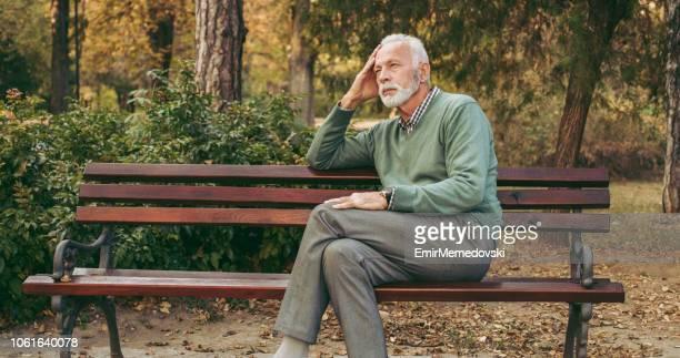 uomo anziano seduto in panchina nel parco - panchina foto e immagini stock