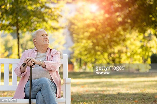 senior man sitting on bench outdoors - walking cane stock photos and pictures