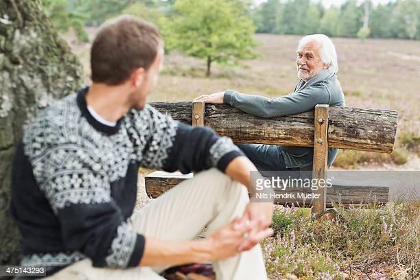 Senior man sitting on bench talking to mid adult man