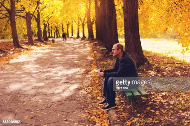 Senior man sitting on bench with hot drink in  autumn park