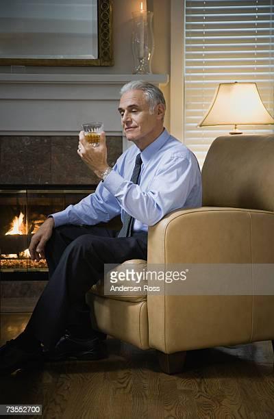 senior man sitting on chair by fireplace, smiling - einzelner senior stock-fotos und bilder