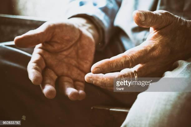 senior hombre sentado en la silla para descansar - entrelazado fotografías e imágenes de stock