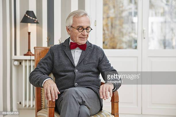 Senior man sitting on chair looking at smartwatch