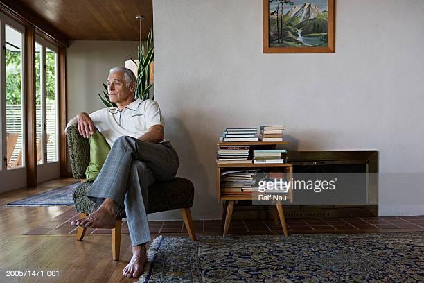 senior man sitting on chair, looking away - 足を組む ストックフォトと画像