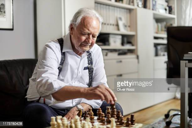 senior man sitting on couch playing chess at home - chess stock pictures, royalty-free photos & images