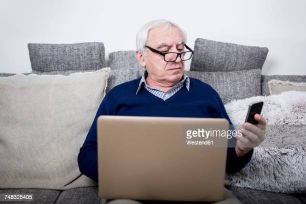 senior man sitting on couch, using laptop and smartphone - suspicion stock pictures, royalty-free photos & images