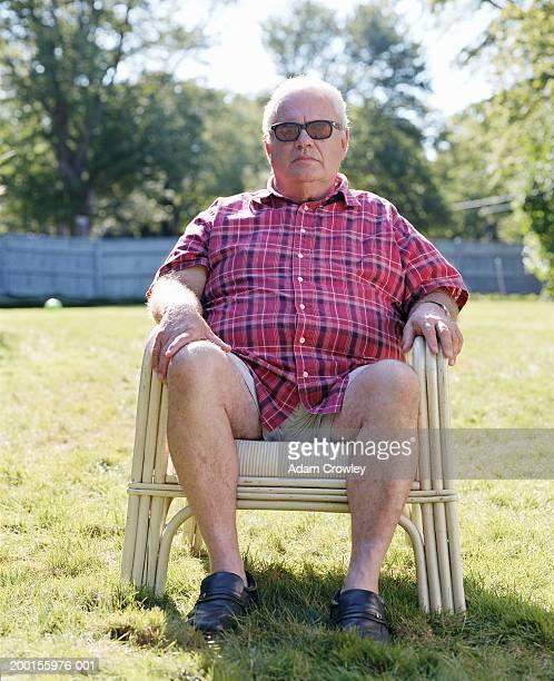 Senior man sitting on deck chair in yard, portrait