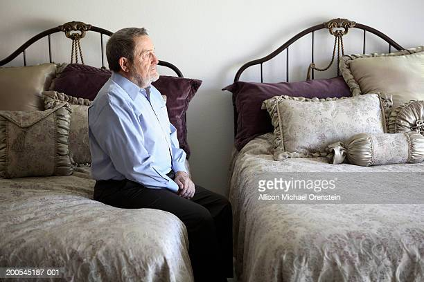 senior man sitting on edge of bed in double bedroom - mourner stock pictures, royalty-free photos & images