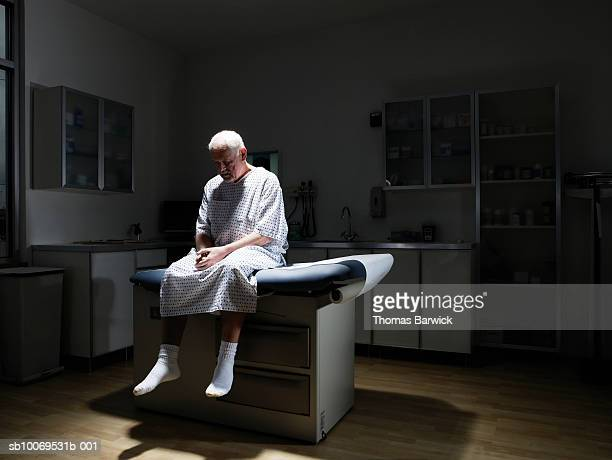 Senior man sitting on examination table, looking down