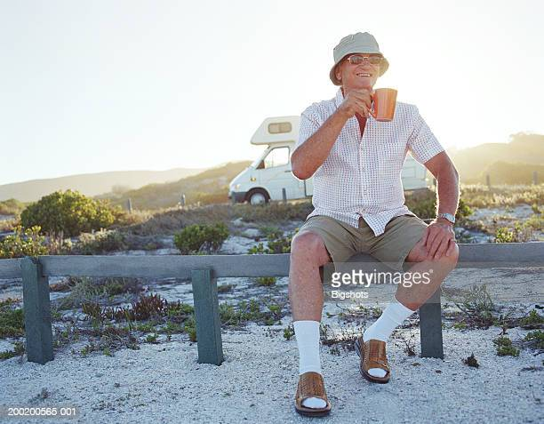 Senior man sitting on fence holding mug, smiling