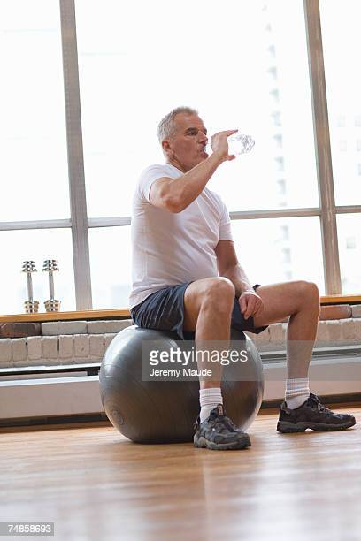 Senior man sitting on fitness ball and drinking water