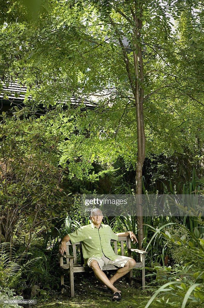 Senior man sitting on garden bench : Foto stock