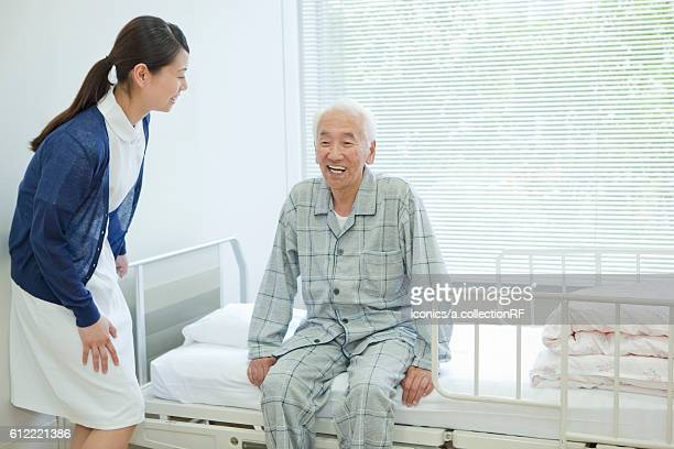 Senior man sitting on hospital bed, Kanagawa Prefecture, Honshu, Japan