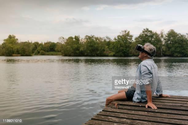 senior man sitting on jetty at a lake wearing vr glasses - einzelner senior stock-fotos und bilder
