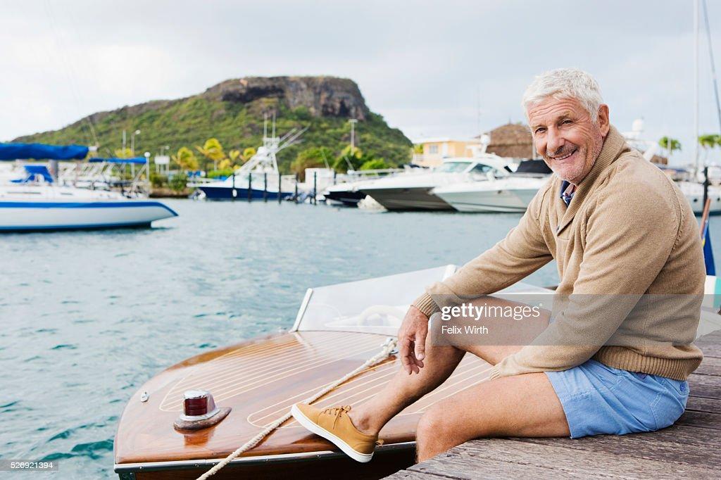 Senior man sitting on jetty : Foto de stock